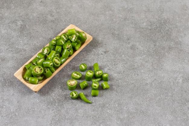 Houten plaat van gesneden chilipepers op stenen tafel.