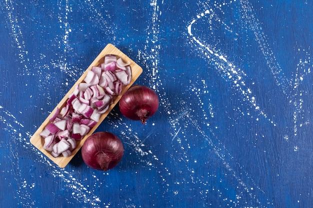 Houten plaat van gesneden en hele paarse uien op marmeren oppervlak