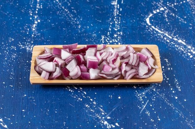Houten plaat van gesneden paarse uien op marmeren tafel.