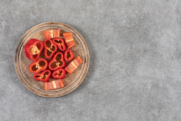 Houten plaat van gesneden verse rode paprika op marmeren oppervlak.