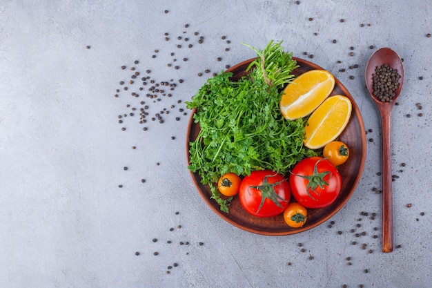 Houten plaat van groenen, tomaten en citroen op stenen oppervlak.