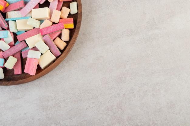 Houten plaat van kleurrijke aromagommen op stenen tafel.