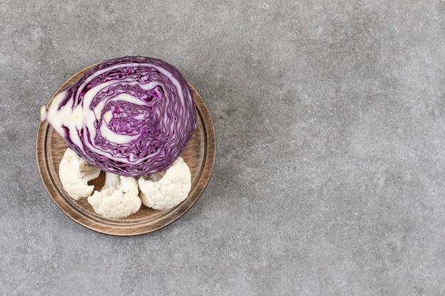 Houten plaat van paarse kool en bloemkool op stenen tafel.
