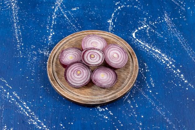 Houten plaat van paarse uienringen op marmeren tafel.