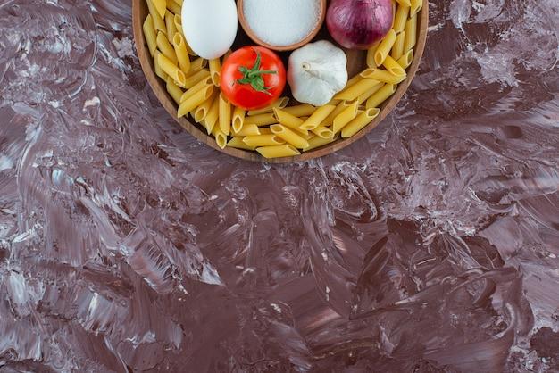 Houten plaat van rauwe penne en groenten op marmeren oppervlak.