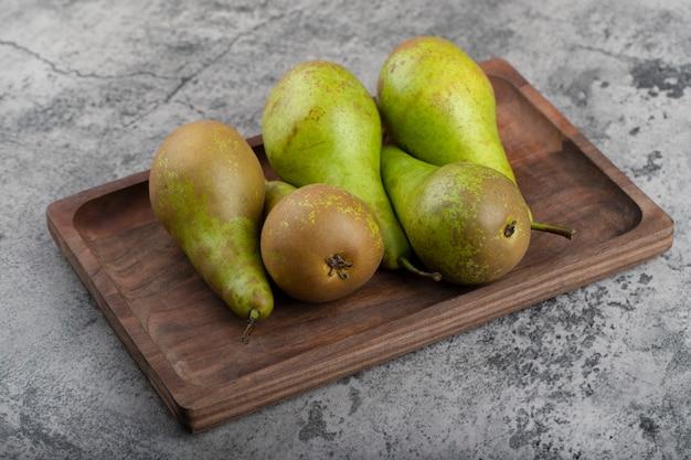 Houten plaat van rijpe groene peren op stenen achtergrond.