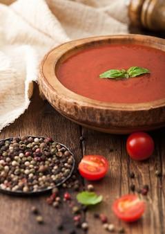 Houten plaat van romige tomatensoep met peper en keukendoek op houten bord. met rauwe tomaten.