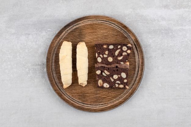 Houten plaat van traditionele zoete mutaki en cacaokoekjes op stenen tafel.