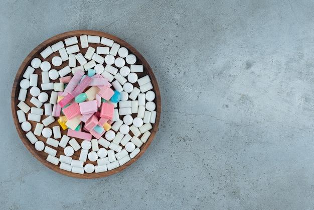 Houten plaat van veel kauwgom op stenen oppervlak.
