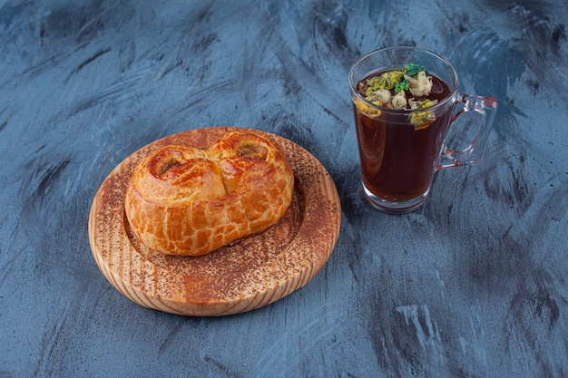 Houten plaat van vers geurig gebak en kopje thee op marmeren oppervlak.
