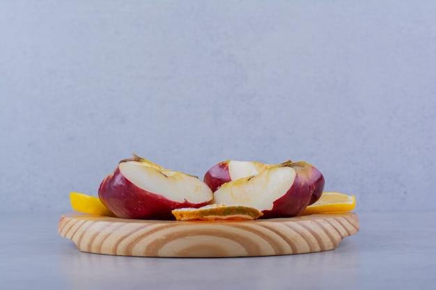 Houten plaat van verse appels en plakjes citroen op stenen tafel.