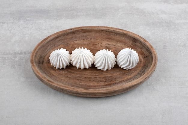 Houten plaat van wit meringue dessert op stenen tafel.