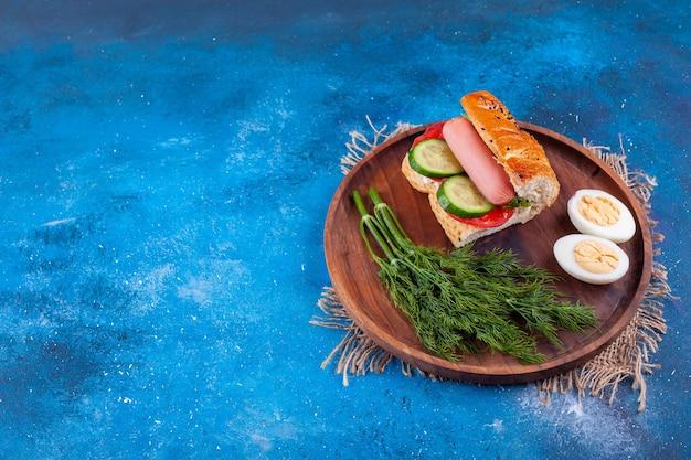 Houten plaat van worst sandwich met dille en eieren op blauwe ondergrond.