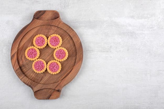 Houten plaat van zoete koekjes met roze hagelslag op stenen tafel.