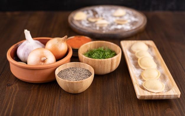 Houten plaat vol met zelfgemaakte dumplings op houten oppervlak.