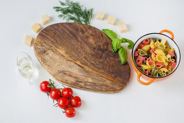 Houten plank, eromheen zijn tomaten, olijfolie, dille, kaas, basilicum en kleurrijke pasta