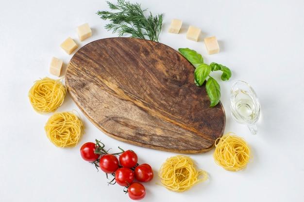 Houten plank, eromheen zijn tomaten, olijfolie, dille, kaas, basilicum en pasta in de vorm van nesten