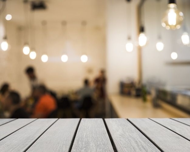 Houten plank kijkt uit naar wazig restaurant scene