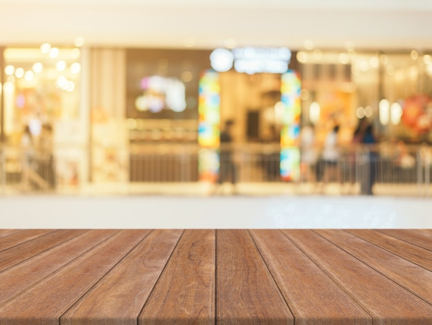 Houten plank lege tabel wazig achtergrond. perspectief bruin hout over onduidelijk beeld in warenhuis