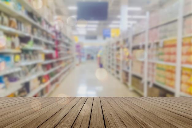 Houten plank lege tafel onscherpe achtergrond. perspectief licht hout over onduidelijk beeld in supermarkt