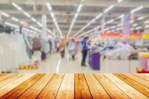 Houten plank lege tafel onscherpe achtergrond. perspectief licht hout over onscherpte in de supermarkt - kan worden gebruikt voor weergave of montage van uw producten. bespotten voor weergave van het product.