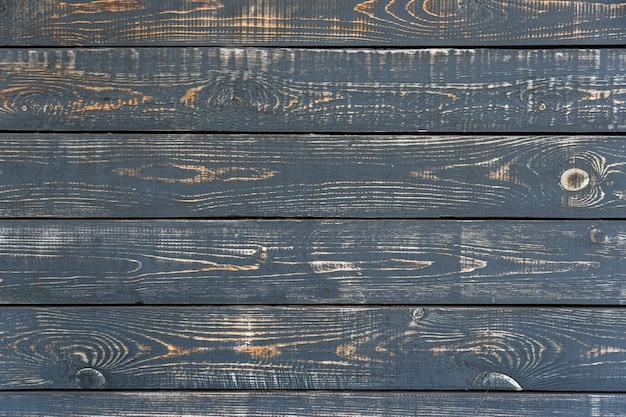 Houten plank met donkere gebarsten verf