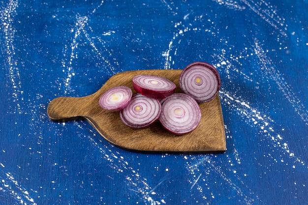 Houten plank met paarse uienringen op marmeren oppervlak