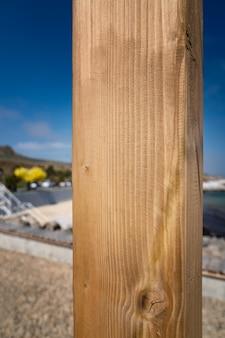 Houten plank op een verticaal tegen de achtergrond van een strand