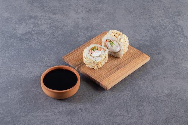 Houten plank van sushi rolt met sesamzaadjes op stenen achtergrond.