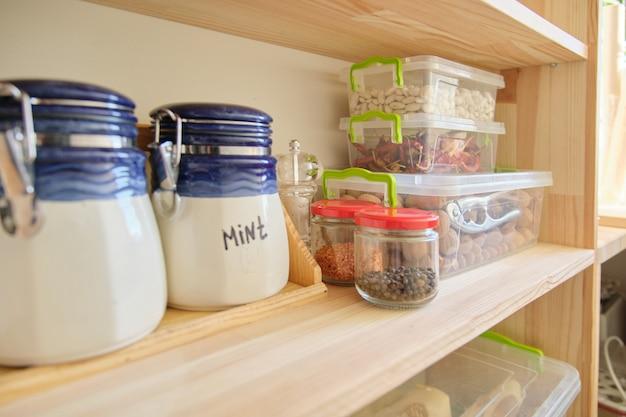 Houten planken met voedsel en keukengerei in de bijkeuken