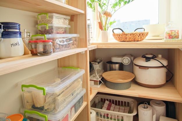 Houten planken met voedsel en keukengerei, keukenapparatuur in de bijkeuken