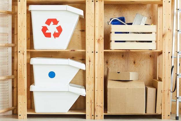 Houten planken met vuilnisbakken en dozen met instrumenten voor reparatie in het magazijn