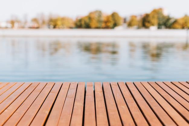 Houten plankenvloer op de achtergrond van een vijver