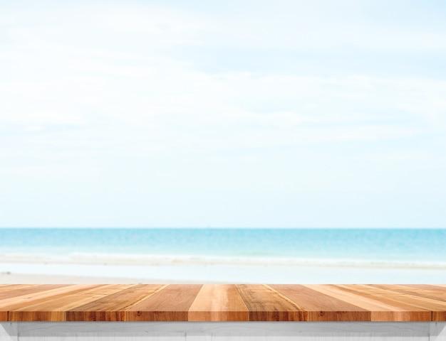 Houten planktafelblad met vage overzees en blauwe hemel bij achtergrond