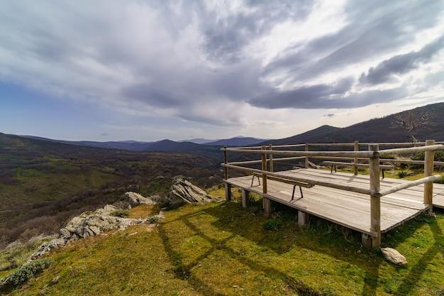 Houten platform om het uitzicht op het groene berglandschap te aanschouwen