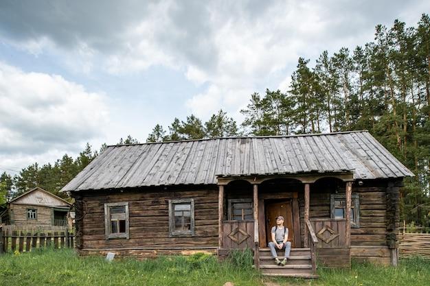 Houten platteland oud huis met zittende man op de veranda