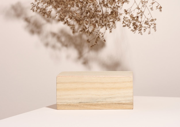 Houten podium om cosmetica en andere items te presenteren, beige achtergrond met droge wilde bloemen en schaduw