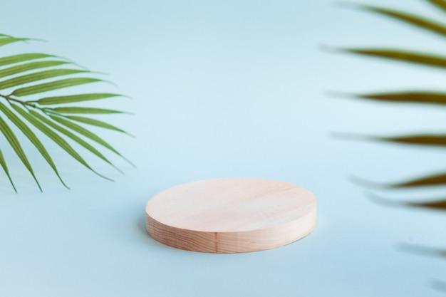 Houten podium voor cosmetisch product palmboom bladeren blauwe achtergrond