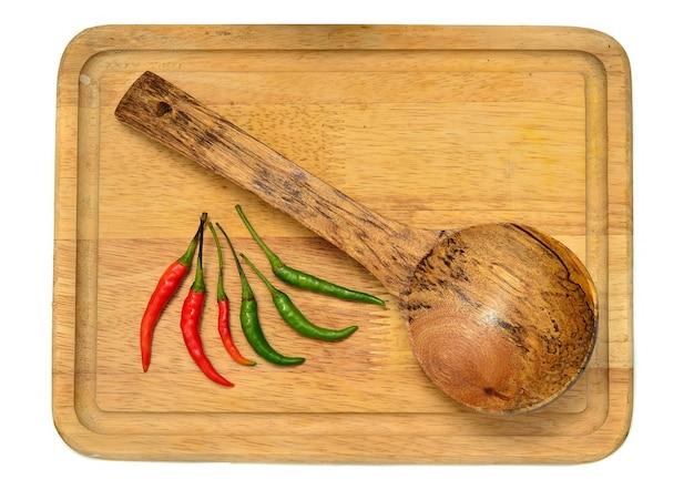 Houten pollepel met rode en groene chili op houten bord