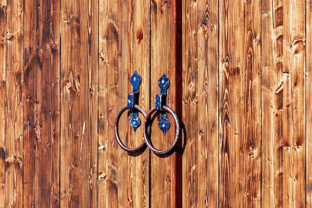 Houten poorten versierd met gesmede metalen elementen