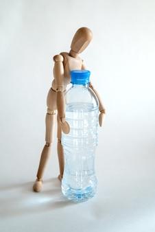 Houten pop pakt een plastic fles water op