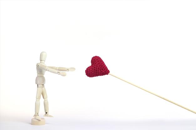 Houten pop reikt naar het gebreide rode hart. het concept van het nastreven van geluk