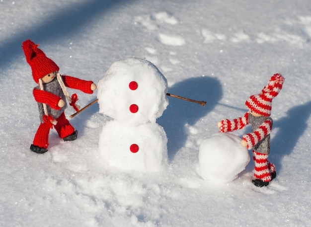 Houten poppen in rode gebreide kleding rollen sneeuwballen naar beneden om een sneeuwpop te bouwen