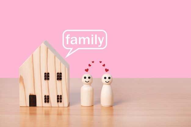 Houten poppenpaar staat voor huismodel op roze achtergrond. gezinswoning, verzekeringen en vastgoedbeleggingen in onroerend goed.