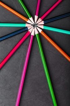 Houten potloden van verschillende kleuren in de vorm van een ster op een zwarte achtergrond. bovenaanzicht