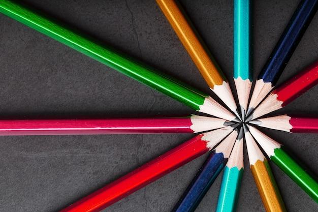 Houten potloden van verschillende kleuren in de vorm van een ster op een zwarte achtergrond.