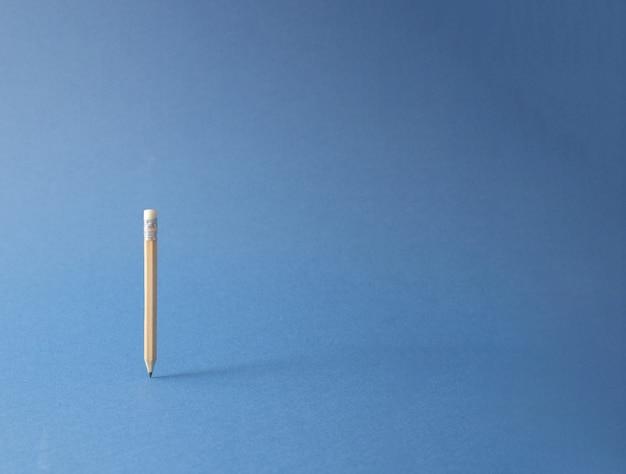 Houten potlood, zwevend. minimaal creatief kantoor / school / bedrijfsconcept. blauwe achtergrond.