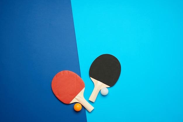 Houten rackets voor het spelen van tafeltennis en een net op een blauwe achtergrond