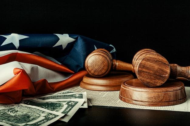 Houten rechter hamer met dollar notities op de vlag van de vs met onafhankelijkheidsverklaring