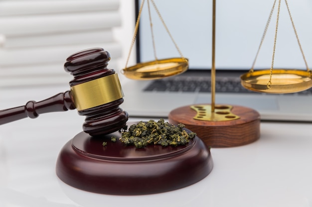 Houten rechter hamer met geluidsblok op de achtergrond van de zwarte spiegel - legaliteit van cannabis, legale en illegale cannabis op de wereld.